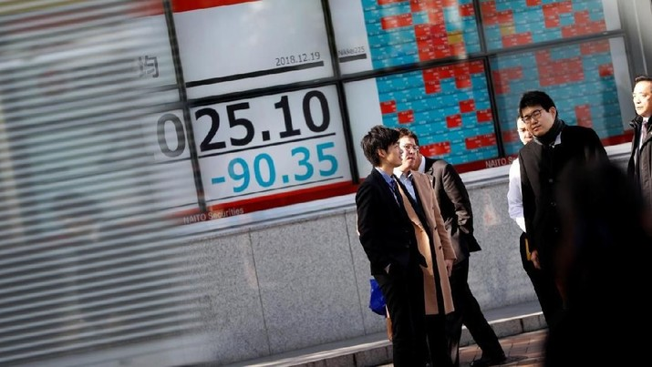FILE PHOTO: Men stand in front of a stock quotation board outside a brokerage in Tokyo, Japan December 19, 2018. REUTERS/Issei Kato