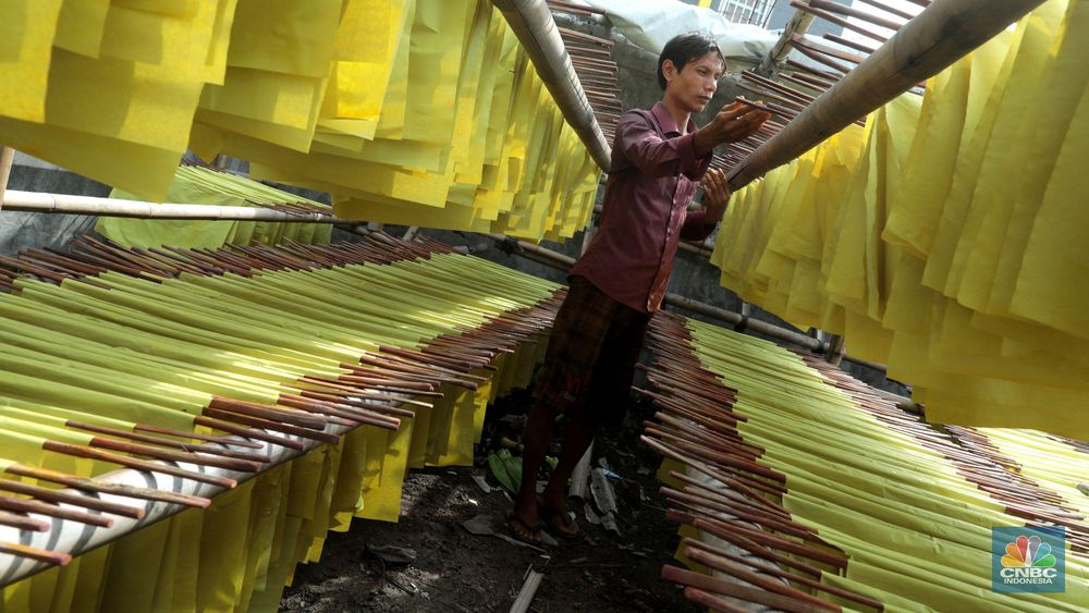 Pekerja menjemur ratusan kertas kuning yang akan diproduksi untuk ritual perayaan tahun baru Imlek di Kampung Melayu Barat, Kecamatan Teluk Naga, Tangerang, Banten, Jumat (18/1). (CNBC Indonesia/Muhammad Sabki)