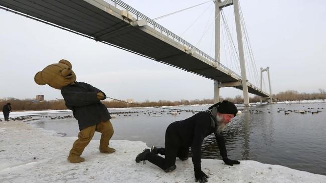 Seorang seniman Vasily Slonov (kanan) dirantai seorang pria berbusana mewah dalam pertunjukan seni berjudul