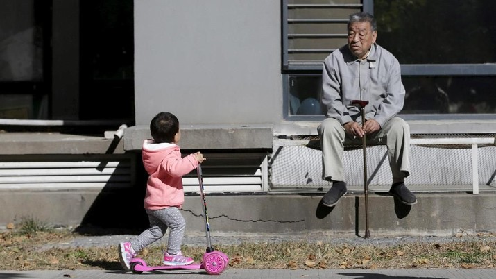 FILE PHOTO: An 80-year-old man, surnamed Li, watches as a girl plays at a residential community in Beijing, China, October 30, 2015. REUTERS/Jason Lee/File Photo
