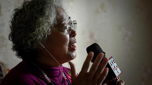 Di beberapa pertunjukan awal, Jinxiang mengaku sering kebingungan mengatasi teknologi ponselnya. (Photo by WANG ZHAO/AFP)