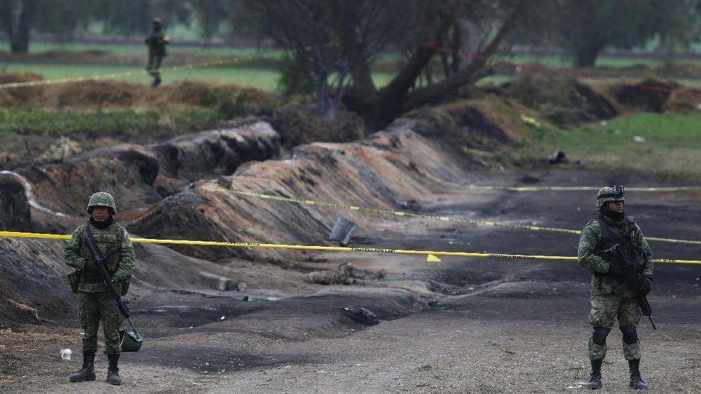 Tentara menjaga tempat kejadian perkara tempat di mana pipa gas meledak dua hari sebelumnya, di desa Tlahuelilpan, Meksiko. Pencurian bahan bakar dari bocornya pipa mengakibatkan ledakan dan kebakaran yang dahsyat sehingga menewaskan puluhan orang. (AP Photo/Claudio Cruz)