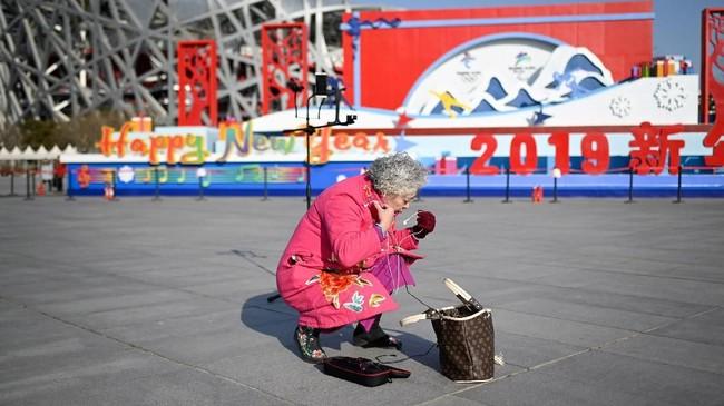 Demikian pula halnya dengan yang dilakukan seorang pensiunan bernama Wang Jinxiang, 62 tahun ini. Bedanya, ia menyiarkan penampilannya itu secara live melalui ponsel.(Photo by WANG ZHAO/AFP)