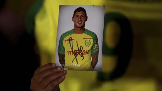 Seorang fan memegang foto dengan tanda tangan Sala di kota Nantes sesaat setelah kabar menghilangnya pesawat yang ditumpangi pemain 28 tahun itu. (REUTERS/Stephane Mahe)