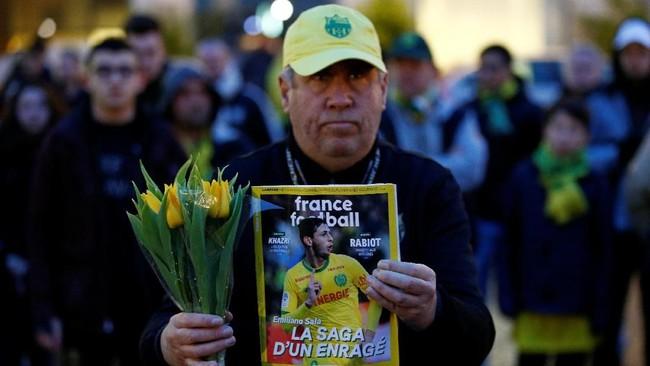 Seorang pria memegang majalah olahraga dan bunga tulip dalam doa bersama di kota Nantes. (REUTERS/Stephane Mahe)