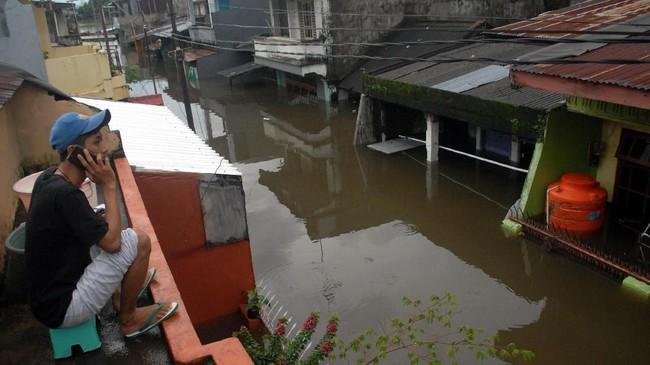 Warga menelpon diatas rumahnya saat banjir di Kecamatan Manggala, Makassar, Sulawesi Selatan, Rabu (23/1/2019). Akibat diguyur hujan dalam beberapa hari sejumlah daerah di Makassar terendam banjir. (ANTARA FOTO/Abriawan Abhe/foc)