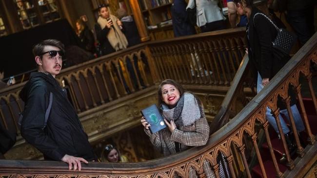 Seorang wanita memegang buku Harry Potter dalam toko buku Lello yang bergaya gothic. Di ambang kebangkrutan, toko buku ini diduga mengilhami J>K> Rowling untuk menulis cerita tentang Potter.(Photo by MIGUEL RIOPA / AFP)