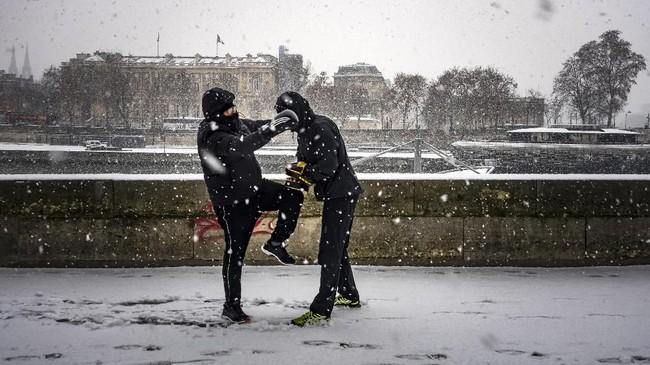 Petinju melakukan latihan di tepi Sungai Seine, Paris, Prancis. (Photo by Lionel BONAVENTURE / AFP)