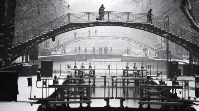 Pemerintah kota Paris berusaha keras menanggulangi dampak turunnya salju pada tahun ini. Para pekerja sudah dikerahkan untuk membuat sistem irigasi salju di jalur-jalur utama sejak Senin (21/1). (Photo by ALAIN JOCARD / AFP)
