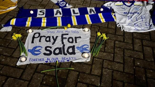 Syal, bunga, dan spanduk terhampar di halaman Stadion Cardiff City seiring dengan kabar menghilangnya pesawat yang ditumpangi Sala. (REUTERS/Rebecca Naden)
