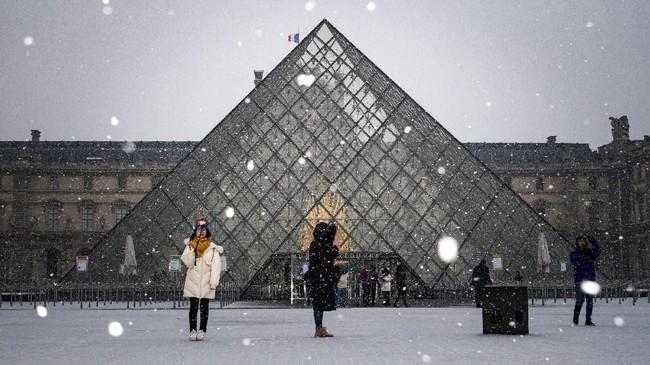 Turis berfoto di depan MuseumLouvre di tengah guyuran salju di Paris, Prancis, yang mulai turun pada pekan ini. (Photo by Lionel BONAVENTURE / AFP)