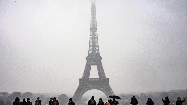 Walau diguyur salju lebat, namun turis masih terlihat menyemut di Menara Eiffel, Paris, Prancis.(Photo by Lionel BONAVENTURE / AFP)
