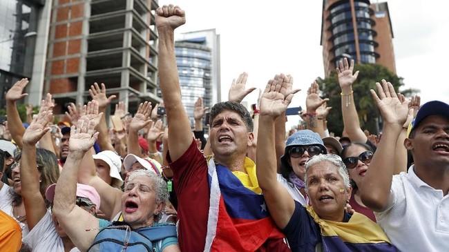 Rakyat pun turun ke jalan dan unjuk rasa memanas pada Selasa (22/1). Demonstrasi di Caracas dan negara bagian perbatasan, Bolivar, mulai ricuh memasuki Rabu dini hari. (Reuters/Carlos Garcia Rawlins)