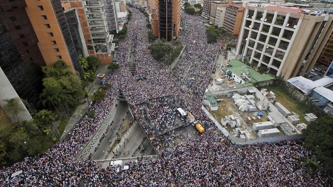 Ribuan warga Venezuela turun ke jalan untuk ikut serta dalam aksi protes anti-Nicolas Maduro yang dianggap tidak pantas duduk di kursi presiden karena berkuasa melalui pemilu tak sah. (Reuters/Adriana Loureiro)