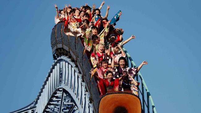 Para perempuan Jepang yang mengenakan kimono bermain di wahana roller coaster saat perayaan akil balig di taman hiburan Toshimaen di Tokyo, Jepang. (REUTERS/Issei Kato)