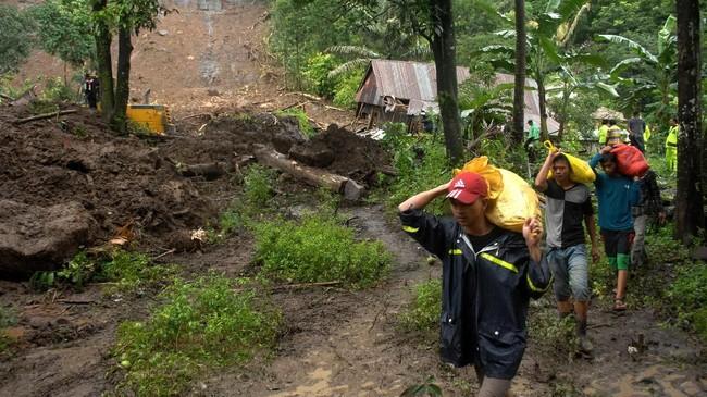Warga mengangkat barangnya di sekitar rumah yang amblas akibat longsor yang terjadi di Kecamatan Mamuju, Kabupaten Gowa, Sulawesi Selatan, Kamis (24/1). (ANTARA FOTO/Abriawan Abhe).
