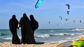 Para perempuan yang mengenakan hijab dan cadar berdiri di suatu pantai di Dubaui sambil menyaksikan layang-layang. (Photo by GIUSEPPE CACACE / AFP)