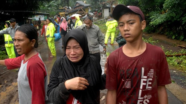 Keluarga korban menangis saat menyaksikan jenazah keluarganya dievakuasi yang menjadi korban yang tanah longsor yang terjadi di Kecamatan Mamuju, Kabupaten Gowa, Sulawesi Selatan, Kamis (24/1). (ANTARA FOTO/Abriawan Abhe).