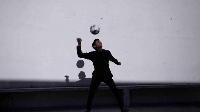 Seorang bocah laki-laki bermain dengan bola di suatu jalanan di Escobedo, area luar kota Monterrey, Meksiko. (REUTERS/Daniel Becerril)