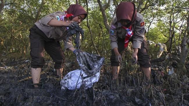 Sejumlah Praja Muda Karana (Pramuka) memunguti sampah plastik di pesisir Tambak Wedi, Surabaya, Jawa Timur, Sabtu (26/1/2019). Kegiatan itu sebagai wujud kepedulian terhadap kebersihan lingkungan di kawasan pantai. ANTARA FOTO/Didik Suhartono/hp.