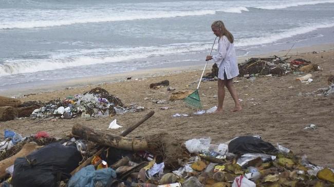 Seorang turis turut membersihkan sampah yang berserakan di kawasan Pantai Kuta, Badung, Bali, Selasa (1/1/2019). ANTARA FOTO/Nyoman Hendra Wibowo/nym.