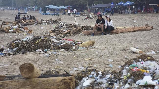 Dua wisatawan duduk di antara tumpukan sampah di kawasan Pantai Kuta, Badung, Bali, Selasa (1/1/2019). Perayaan malam tahun baru di Pantai Kuta menambah volume sampah yang berserakan bercampur dengan sampah yang terdampar akibat cuaca. ANTARA FOTO/Nyoman Hendra Wibowo/nym/nz.