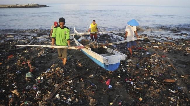 Nelayan menepikan perahunya melewati tumpukan sampah yang berserakan di Pantai Muara Lasak, Padang, Sumatera Barat, Kamis (24/1/2019). Nelayan mengeluhkan sampah dari hulu yang bertumpuk sejak Senin (22/1) karena menghambat akses perahu mereka untuk pergi melaut. ANTARA FOTO/Iggoy el Fitra/aww/