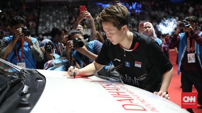 Liliyana Natsir membubuhkan tanda tangan di salah satu mobil sponsor yang terparkir di dalam Istora Senayan usai final Indonesia Masters 2019. (CNN Indonesia/Andry Novelino)