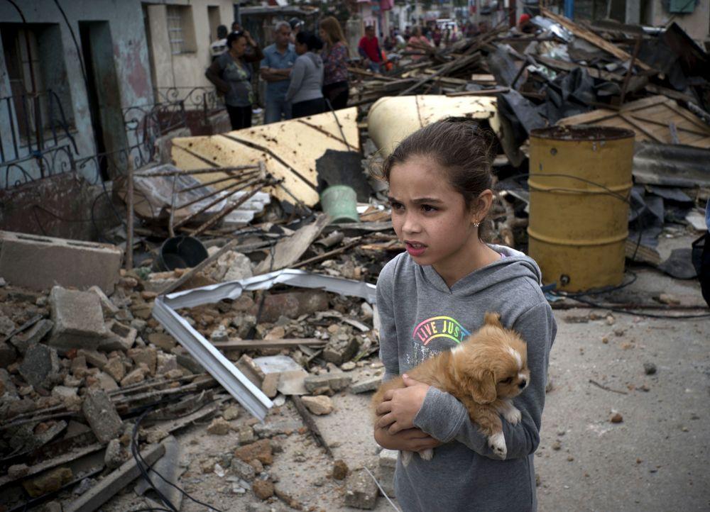 Seorang gadis dengan anak anjingnyaberjalan di samping reruntuhan bangunanyang rusak akibat tornado yang melanda Havana, Kuba, Senin (28/1/2019).Sebuah tornado menerjang sejumlah pemukiman di Havana yang menyebabkan korban jiwa dan luka-luka.(AP Photo/Ramon Espinosa)