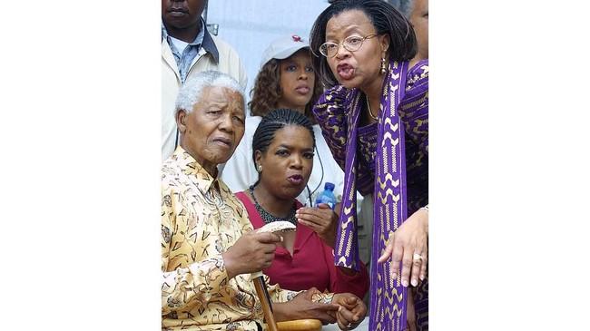 Bukan hanya dengan politisi Amerika Serikat. Bukti Oprah memiliki pengaruh mendunia adalah kala dirinya bisa dekat dengan mantan Presiden Afrika Selatan Nelson Mandela (kiri) dan istrnya pada 22 Desember 2002. Kala itu, Oprah diundang hadir di pesta Natal di kediaman Mandela. (RAJESH JANTILAL / AFP)