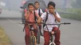 Asap yang dihasilkan mengganggu warga. Tampak sejumlah siswa menutup hidung agar tak menghirup asap. Kabut asap membuat dengan jarak pandang hanya 30 - 70 meter. (ANTARA FOTO/Syifa Yulinnas)