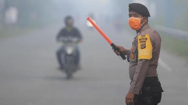 Untuk mengantisipasi kecelakaan lalu lintas karena jarak pandang terbatas membuat personel Polres Aceh Barat mengatur lalu-lintas jalan nasional Medan-Banda Aceh. (ANTARA FOTO/Syifa Yulinnas)