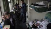 Di gerbong tidur suasana meriah terdengar sahut menyahut, keluarga mengobrol sambil menyantap makanan dan anak-anak bermain dengan seru. (Nicolas ASFOURI / AFP)