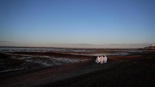 Jemaat wanita terlihat berdoa dan bernyanyi ketika matahari terbit di hari baptis massal diselenggarakan, 25 Agustus 2018 silam. (REUTERS/Simon Dawson)