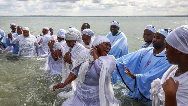 Para jemaat yang sedang melakoni pembaptisan massal yang disebut Jorodhani di tepi pantai tampak saling berinteraksi. (REUTERS/Simon Dawson)