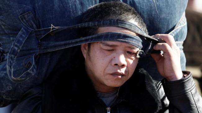 Seorang pemudik membawa tas besar menuju East Railway Station di Zhejiang, China.(REUTERS/Jason Lee)
