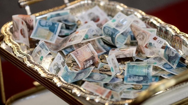 Sterling notes sit on a collection tray during a Good Friday Lent church service at the Eternal Sacred Order of Cherubim & Seraphim Church in London, Britain, March 30, 2018. The church was founded by Moses Orimolade Tunolase in 1925 in Nigeria and is attended by worshippers of Nigerian descent who come from all over the country for services. REUTERS/Simon Dawson