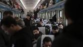 Selama perjalanan selama 32 jam dari Beijing ke Huaihua di provinsi Hunan, China tengah, para pemudik menghibur di telepon seluler sambil menyeruput teh dari termos. (Nicolas ASFOURI / AFP)