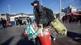Di Stasiun Kereta Api Beijing pada Rabu (30/1) pagi, ribuan orang berseliweran dalam cuaca dingin, terbungkus mantel tebal sambil membawa barang bawaan mereka. (REUTERS/Jason Lee)