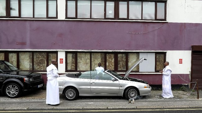 Seorang pendoa mendoakan mobil yang akan digunakan untuk mengangkut para jemaat Gereja Christ Grace of God Parish di London. (REUTERS/Simon Dawson)