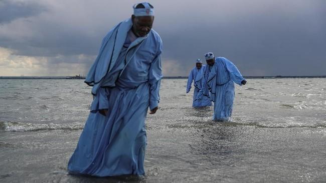 Jemaat senior Gereja Apostles Of Muchinjikwa meninggalkan laut setelah memimpin baptis massal di pantai di Inggris. (REUTERS/Simon Dawson)