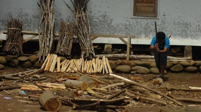 Warga memotong kayu bakar untuk persedian bahan bakar memasak di Kampung Naga, Kabupaten Tasikmalaya, Jawa Barat. (ANTARA FOTO/Adeng Bustomi)