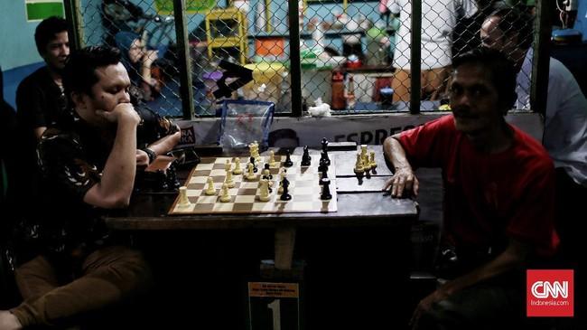 Warga menikmati waktu senggang di sore hari dengan bermain catur di depan warung kampung Ampiun. (CNNIndonesia/Andry Novelino)