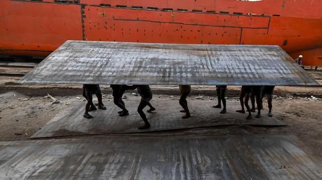 Pekerja Bangladesh membawa plat baja di suatu dermaga di sungai Buriganga di Dhaka. Dermaga-dermaga itu sudah beroperasi tanpa izin selama 50 tahun terakhir sehingga menyebabkan sungai tercemar. (Photo by MUNIR UZ ZAMAN / AFP)