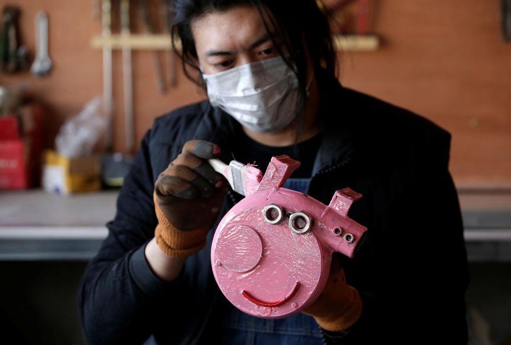 Geng Shuai, menggambar karakter serial animasi Peppa Pig di bengkelnya di desa Yangcun, Baoding, provinsi Hebei, China. Geng sering membuat barang-barang aneh dari barang bekas. (REUTERS/Jason Lee)