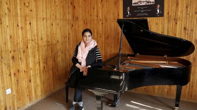 Maram Atayee (16) yang merupakan pianis khawatir jika Taliban kembali maka dia tidak bakal bisa bermain alat musik lagi. (REUTERS/Mohammad Ismail)