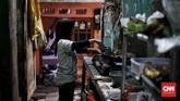Seorang warga memasak di depan rumahnya di gang sempit Ampiun. Kondisi rumah di kawasan ini sangat memprihatinkan karena rata-rata hanya memiliki satu kamaryang dihuni satu keluarga. (CNNIndonesia/Andry Novelino)