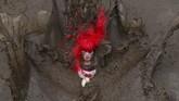 Seorang peserta terjatuh di kolam lumpur saat mengambil bagian dalam ajang ketahanan Tough Guy di Wolverhampton, Inggris. Para peserta ajang ini harus menempa diri mereka melewati ratusan rintangan termasuk air, api, dan terowongan. (Photo by OLI SCARFF / AFP)