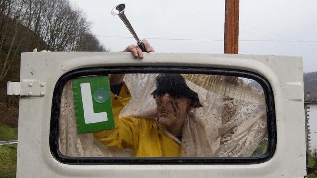 Seorang pemuka agama bertopeng memegang pintu mobil saat merayakan karnaval Zubieta di Provinsi Navarra, Spanyol. Festival itu digelar selama tiga hari merayakan hewan ternak dan hasil bumi. (Photo by ANDER GILLENEA / AFP)
