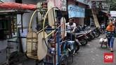 Seorang pria mengayuh 'kincir' untuk anak-anak, hiburan untuk anak-anak kecil di kawasan kampung Ampiun. (CNN Indonesia/Andry Novelino)